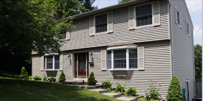 A large, well-maintained Center Hall Colonial with a large yard and pool.