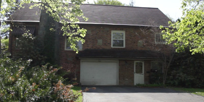 A brick Cape Cod on a corner lot with enchanting gardens.
