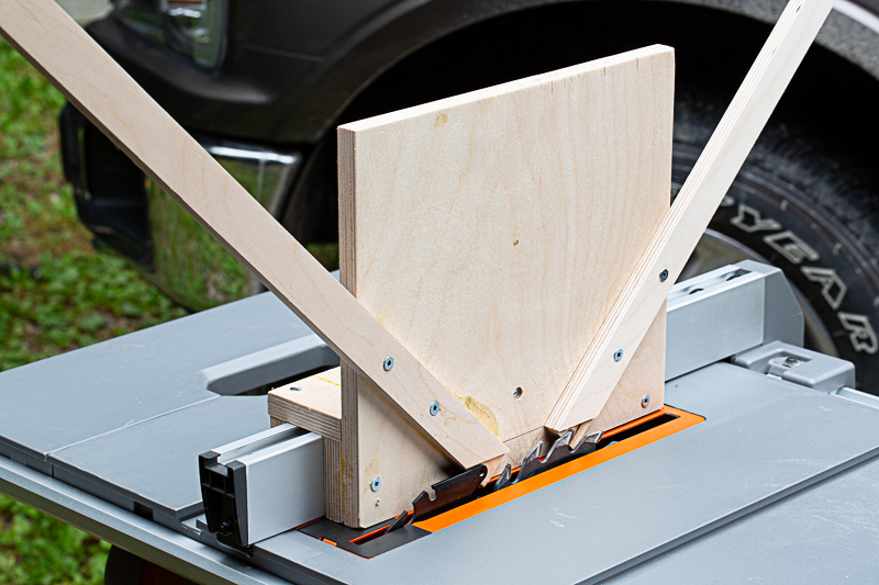 Here you place the frame in the 'jig' with the corner on the table, and push it through the spinning blade to cut a slot.