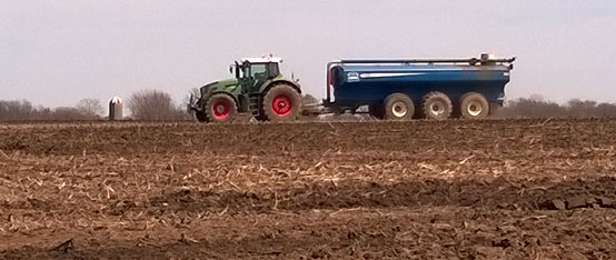 A tractor spreading liquid manure ona cornfield. This farm will need to follow ever-changingrules aboutpreventing runoff, reducing odor, and keeping records to maintain protection under the Right to Farm Act. Ravenna, Michigan (2014).  Photo by the author.