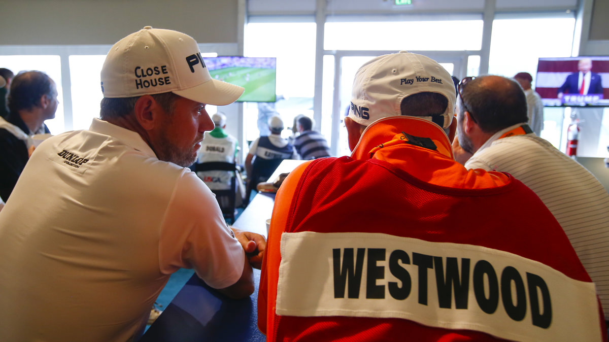 Lee Westwood and his caddie, Billy Foster, sit in the media dining room to watch the England versus Wales soccer game on TV while in a rain delay during the first round for the 2016 U.S. Open at Oakmont Country Club. Copyright USGA/Jeff Haynes