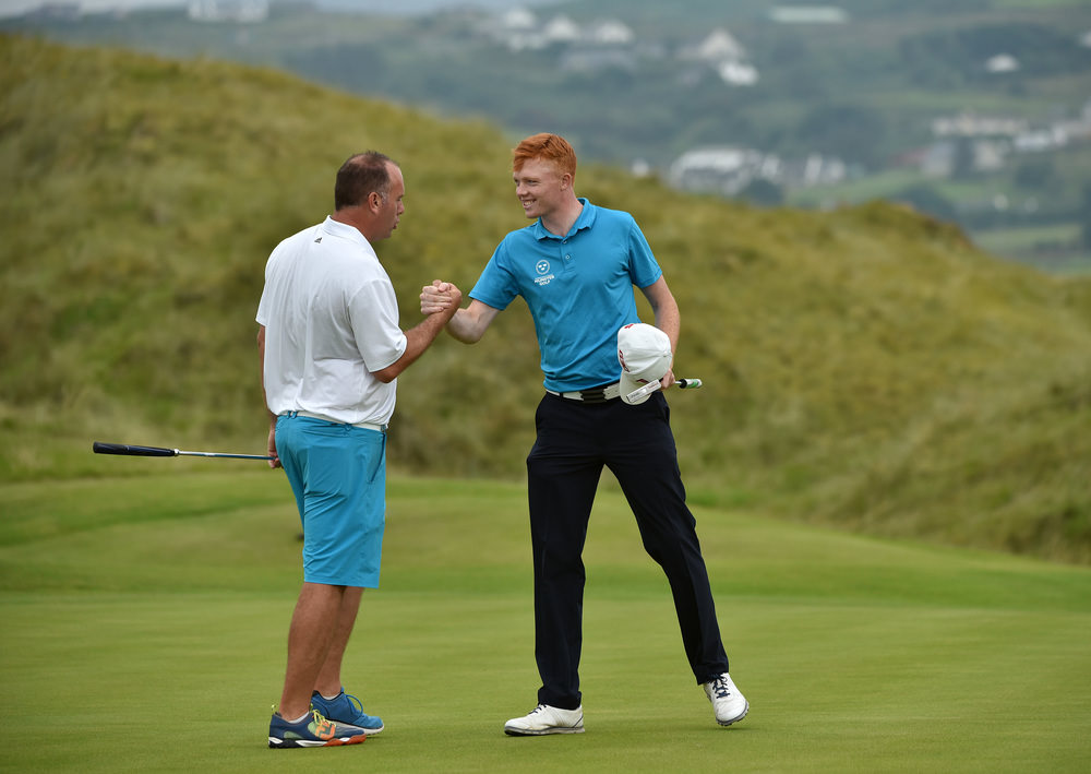 Robin Dawson (Tramore / Maynooth University) is congratulated by Ben Best (Rathmore) after his victory on the 18th green in round two of the AIG Irish Amateur Close at Ballyliffin Golf Club.  Picture by   Pat Cashman