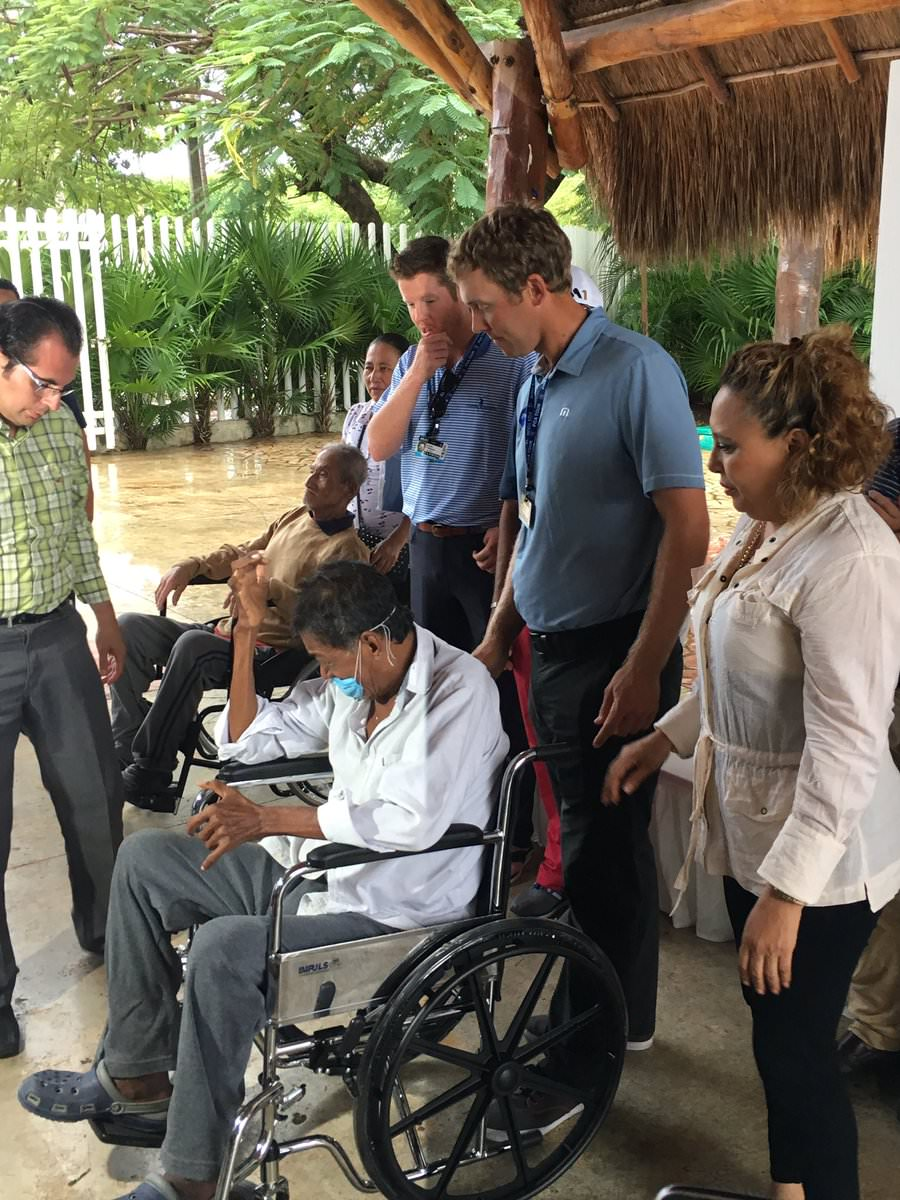 Seamus Power presents a wheelchair to a local man at the OHL Classic at Mayakoba
