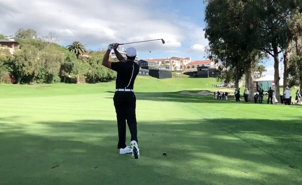 Tiger Woods watches the flight of his approach to the 18th at The Riviera Country Club ahead of the Genesis Open in Los Angeles