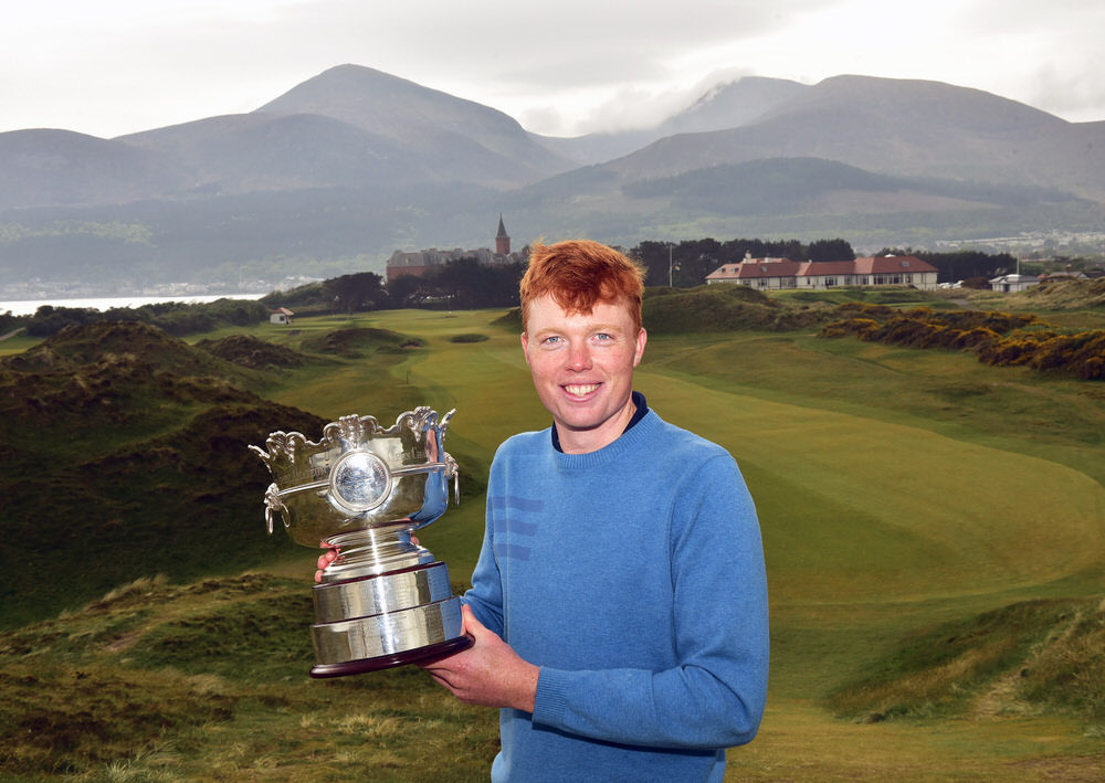 Robin Dawson (Tramore) shows off the Flogas Irish Amateur Open Championship trophy at Royal County Down Golf's famous ninth hole. Picture by  Pat Cashman