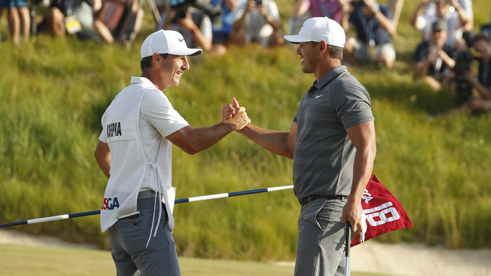 Brooks Koepka shakes hands with his caddie Ricky Elliott on the 18th green after they won their second consecutive U.S. Open during the final round of the 2018 U.S. Open at Shinnecock Hills Golf Club in Southampton, N.Y. on Sunday, June 17, 2018. (Copyright USGA/John Mummert)