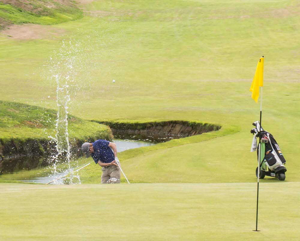 Leading qualifier Ronan Mullarney (Galway) took his shoes and socks off to play a great shot out of the water at the 18th, but it was not enough to keep the match alive and he lost by 1-hole to Dylan Brophy (Castleknock). Picture © Gerry Ruddy
