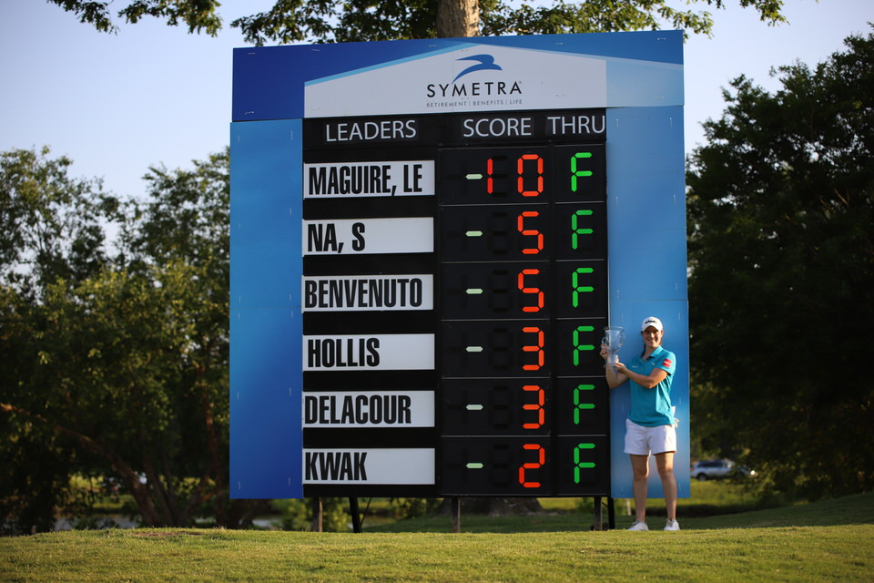 Leona Maguire with trophy at leaderboard (distance).JPG