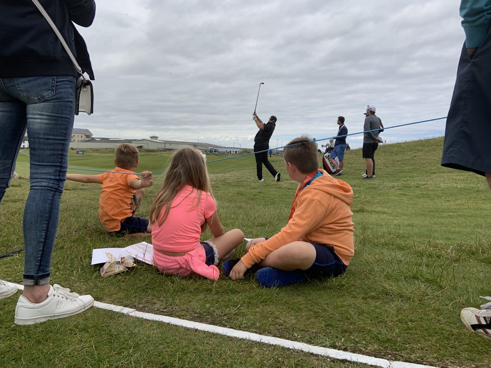 Young fans look on as Shane Lowry hits his approach to the second at Lahinch on Tuesday