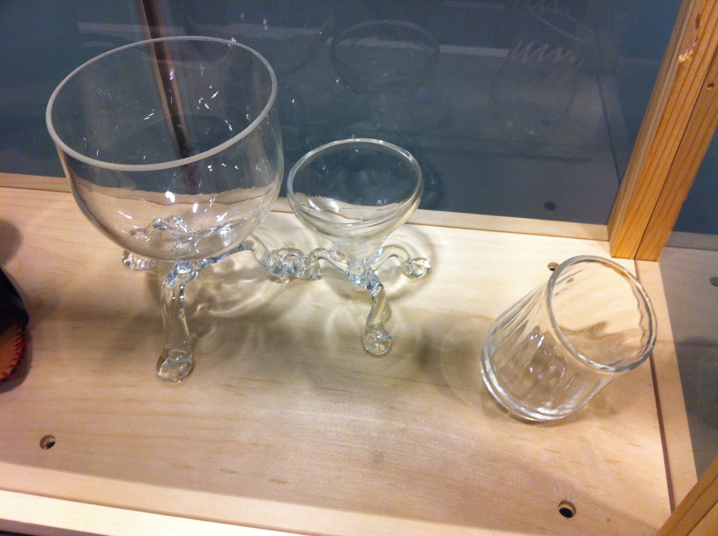 A three legged Goblet. A three legged martini glass. A glass with a curved base to discourage putting it down.