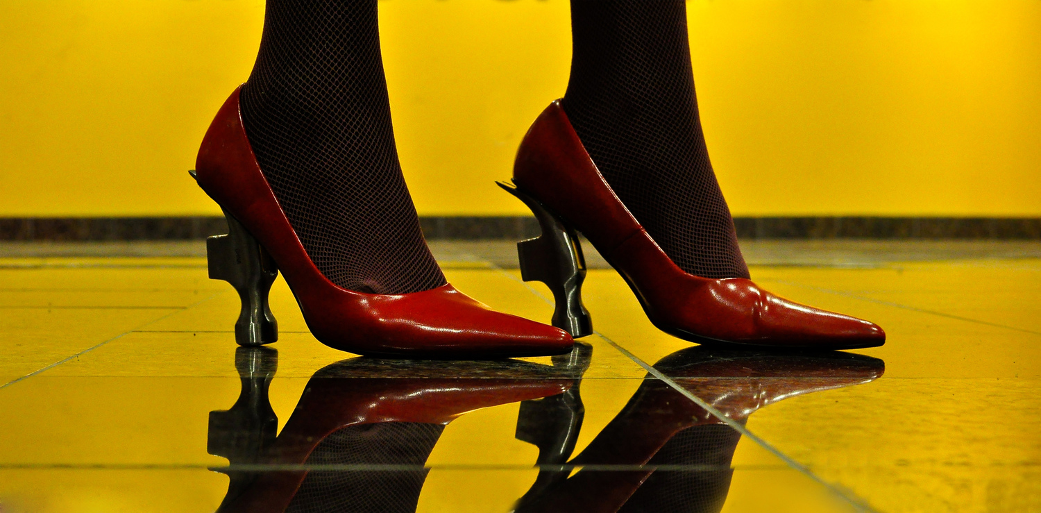 These lipstick red heels were just another accessory to a woman's occasional night out. Nowthe heelshave power, standing tall on the head of a hammer,nailing the ground and pronouncing every step. Walking with aniconic male symbol at her feet, judgement changes.    © Tyler Scholl