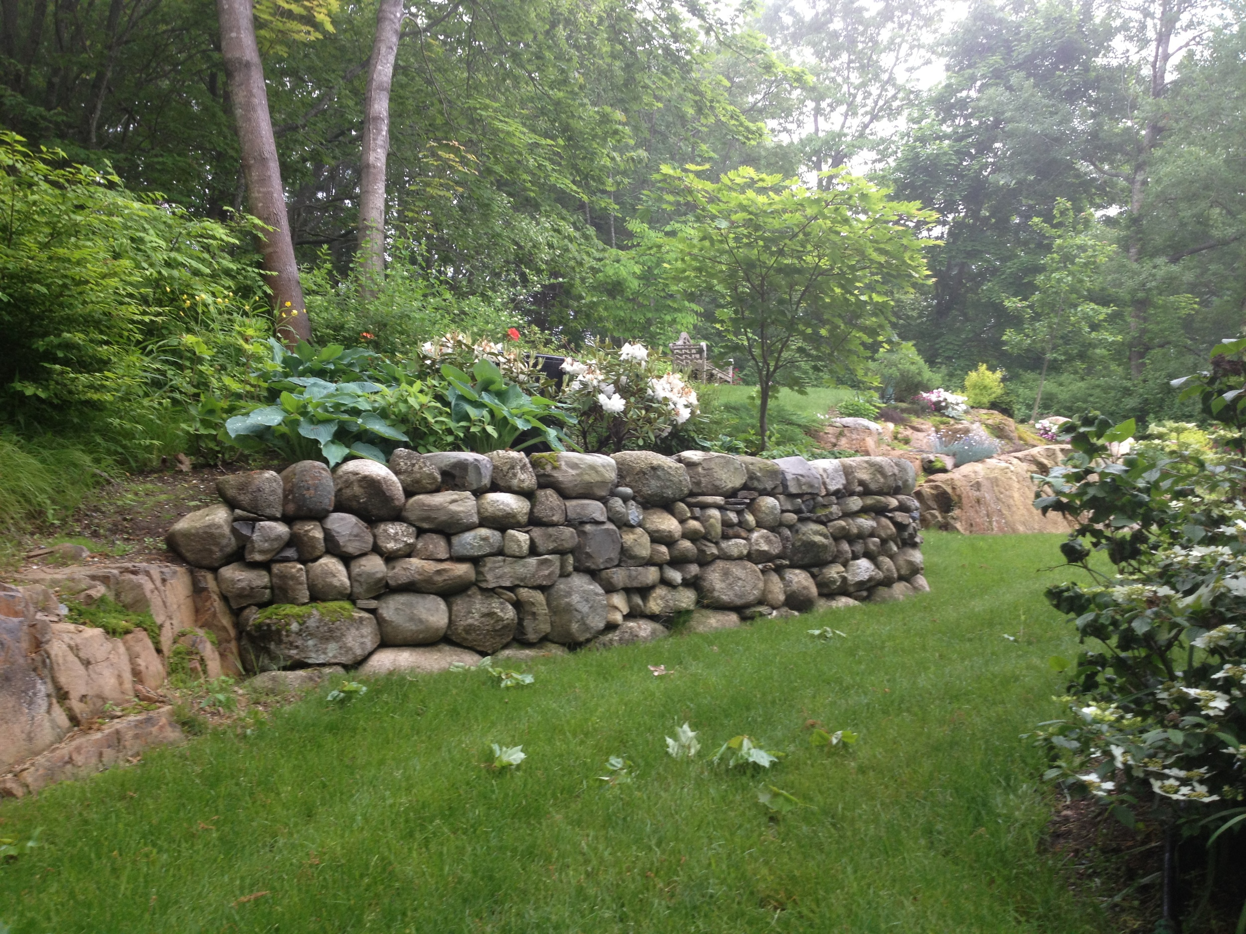 An old English-style garden is enhanced by the dry stonewall feature
