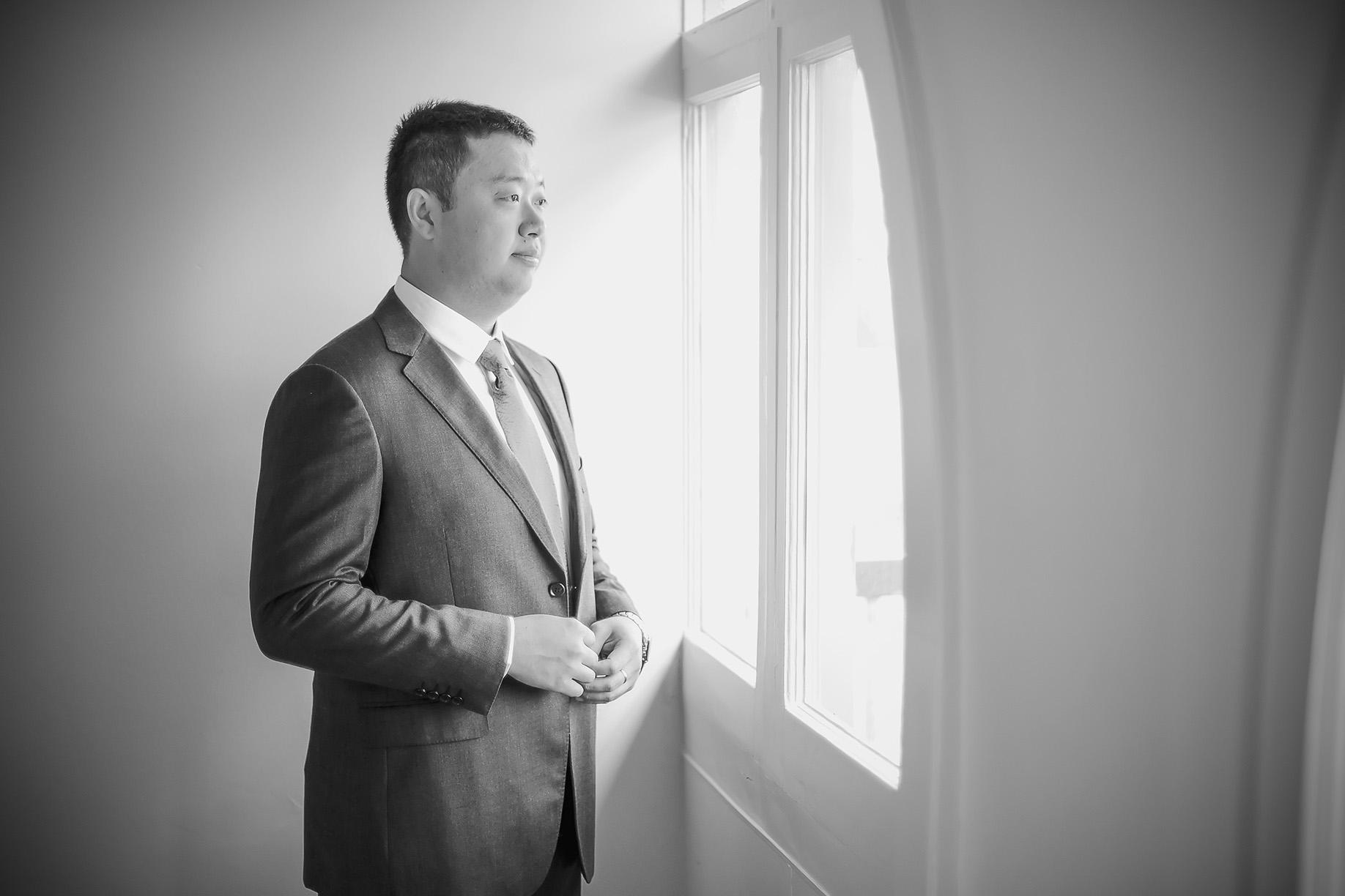 Black and white film style groom preparation photo 4