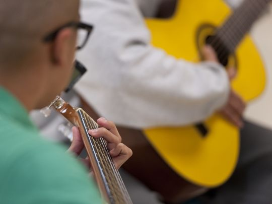 Youth at Tulare County Probation Youth Facility learn guitar from Carlos Rodriguez of Mezcal on Monday, December 14, 2015. Students must behave in and out of all classes to participate in the extracurricular activity.   (Photo: Ron Holman)