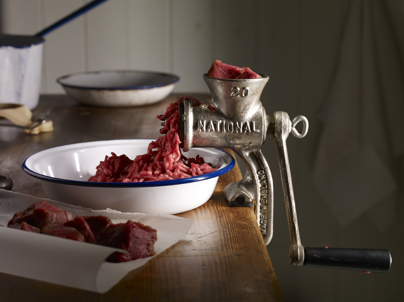 Mincing meat with old hand-operated mincer