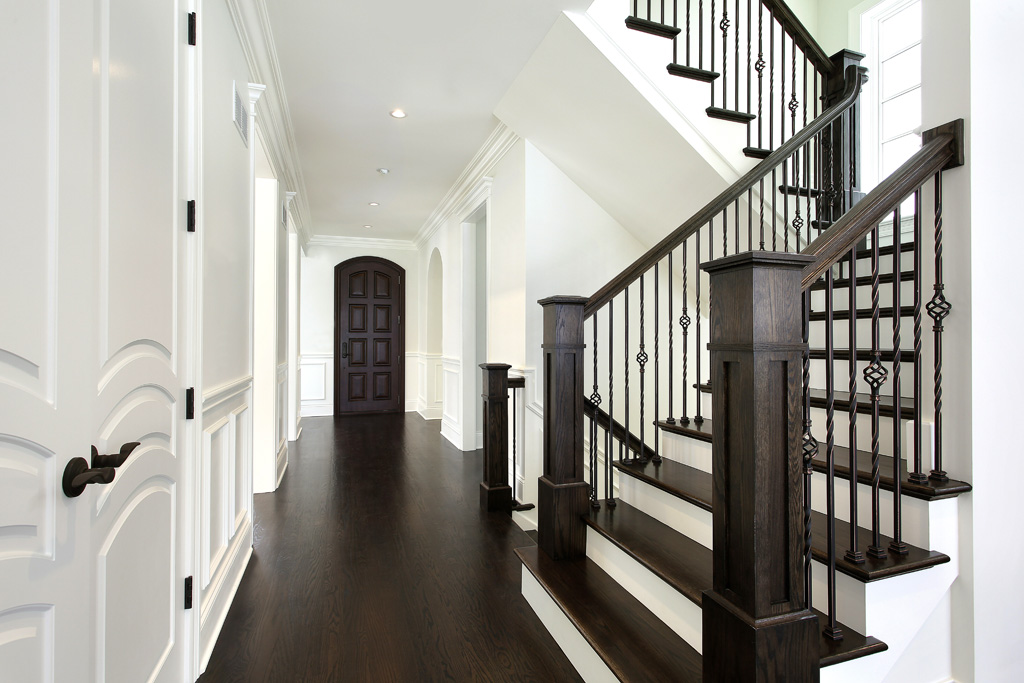 """Custom recessed box newels provide contrast and detail to a """"scissor"""" staircase. Metal BAS1 and TW1 Oil Rubbed Copper balusters give the staircase added drama and beauty."""