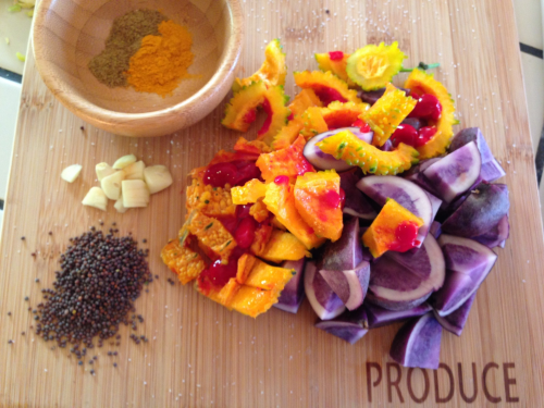 A colorful array of Indian bitter melon and purple potatoes, spiced with garlic, mustard seed, curry and turmeric powder.