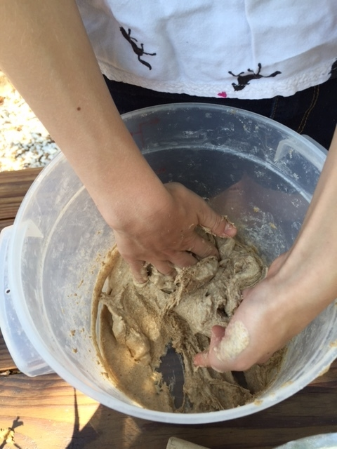 Making dough, hands thick with yeast, flour and salt.