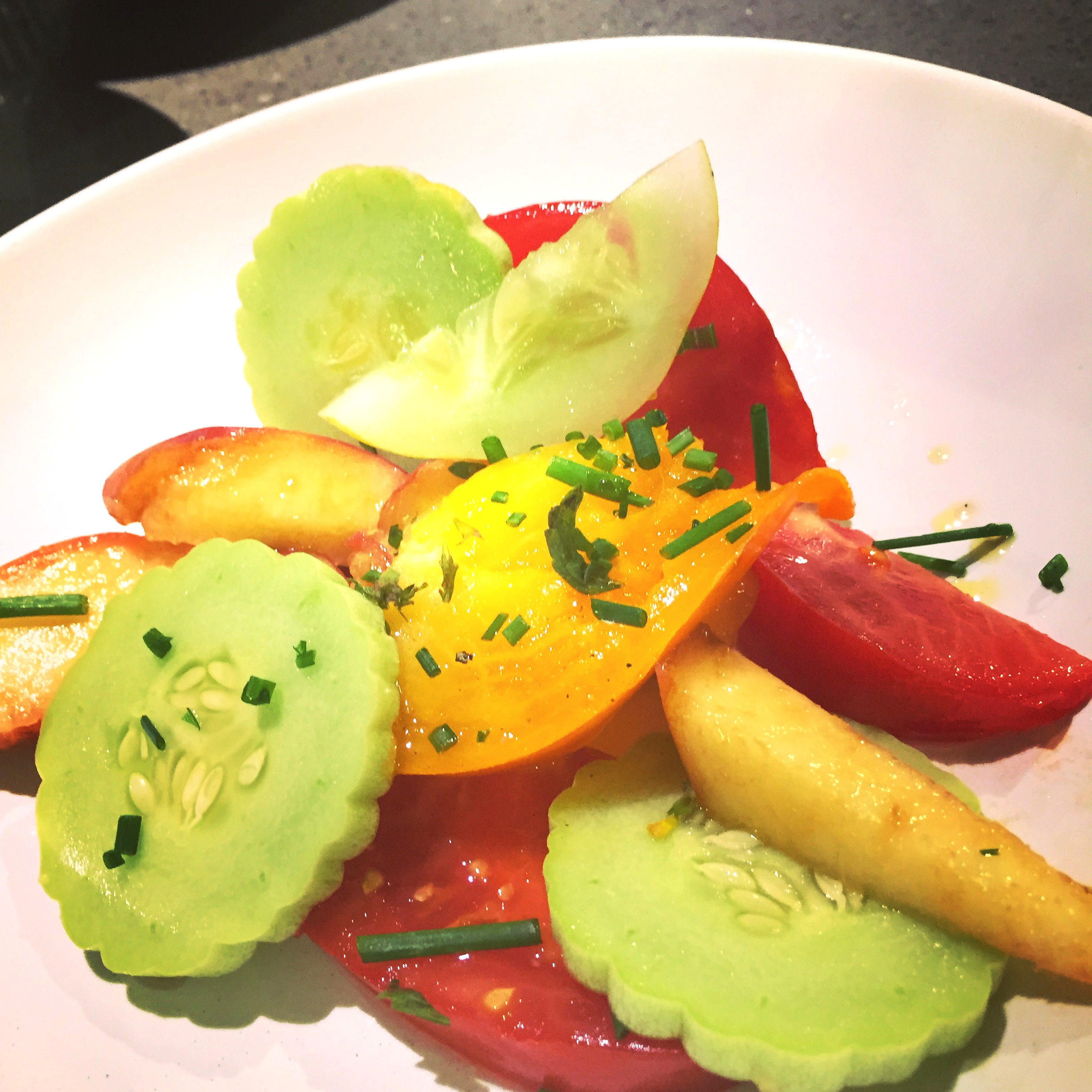 Cool as a cucumber salad with tomatoes & peaches garnished with chives