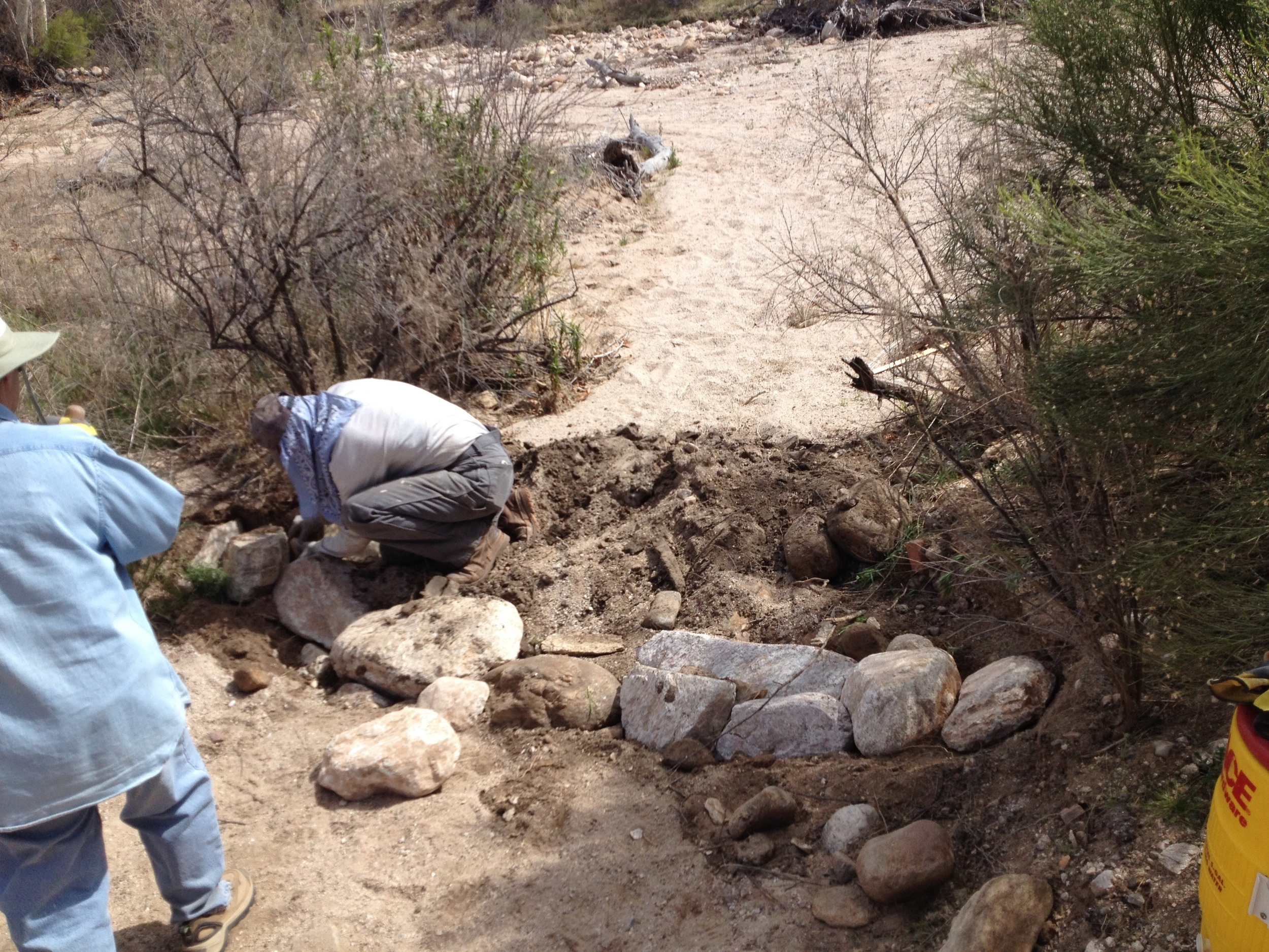 Work begins on the first one rock dam at the mouth of the arroyo.