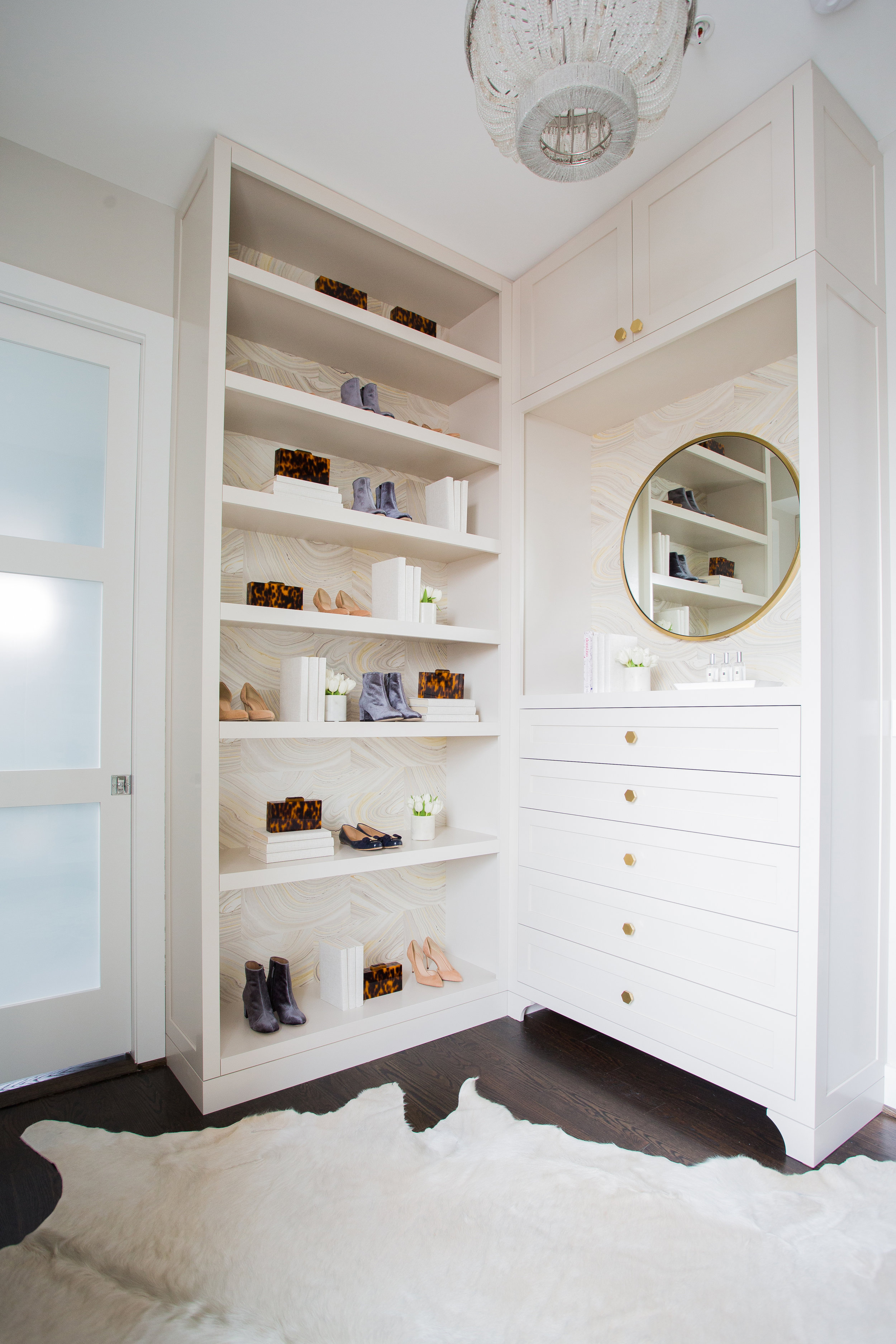 Custom walk-in master closet;birch plywood w/ solid five-piece drawer fronts, wall papered backing, brass hex pulls, round mirror with brass frame