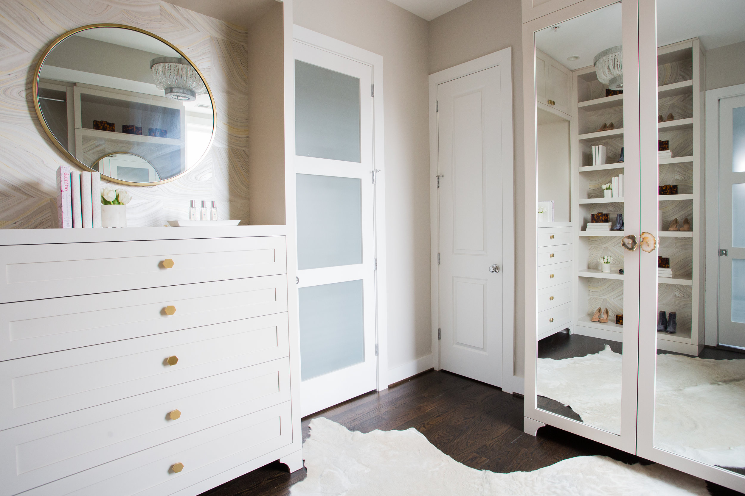 Custom walk-in master closet;birch plywood w/ solid five-piece drawer fronts, wall papered backing, brass hex pulls, custom full-length mirrored doors