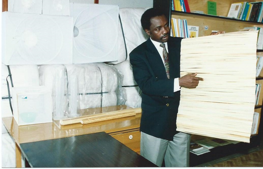 Alfred Latigo who Instigated Research on Insecticide Impregnated Papyrus Mat Explains the Concept and its Affordability and Effectiveness Compared to Existing Outdoor/Indoor Mosquito Control Measures.  GIDE Has Been Involved in Among other Areas, Comparative Impact Evaluation of Insecticide Impregnated Mosquito Nets (in the background) and Papyrus Mats (being held) for Controlling Malaria Transmitting Mosquitoes in East Africa (1992 - 1995)
