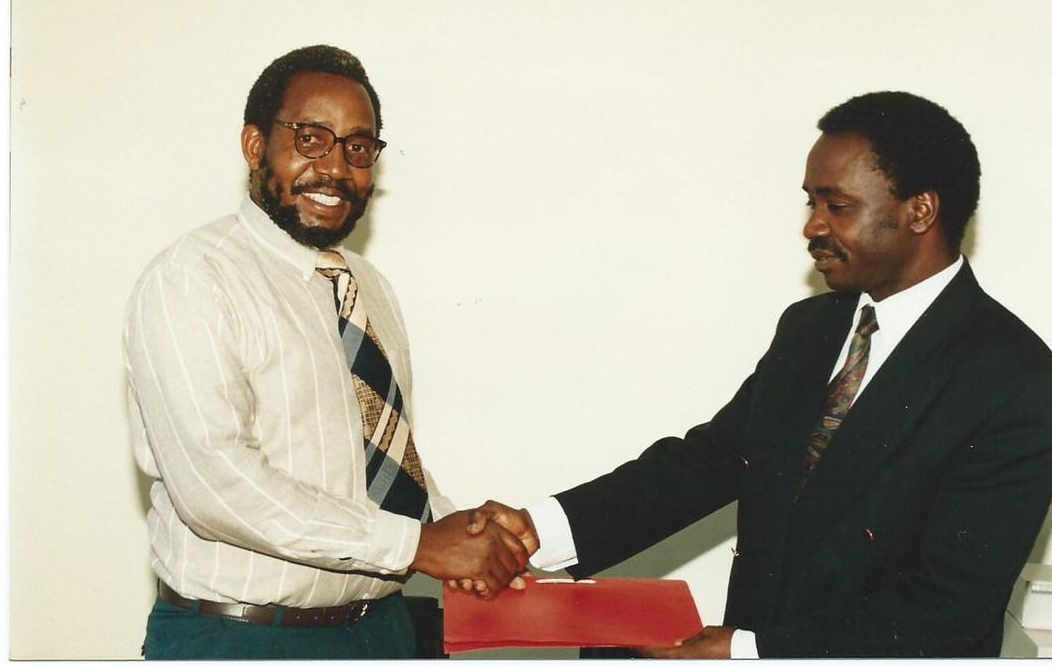 Dr. Alfred Latigo and Dr. Frank Mosha Exchanging an Agreement on Collaborative Biodiversity Prospecting Research Project  between the Tropical Pesticide Research Institute (TPRI), Tanzania and ABI-GIDE  (1995)