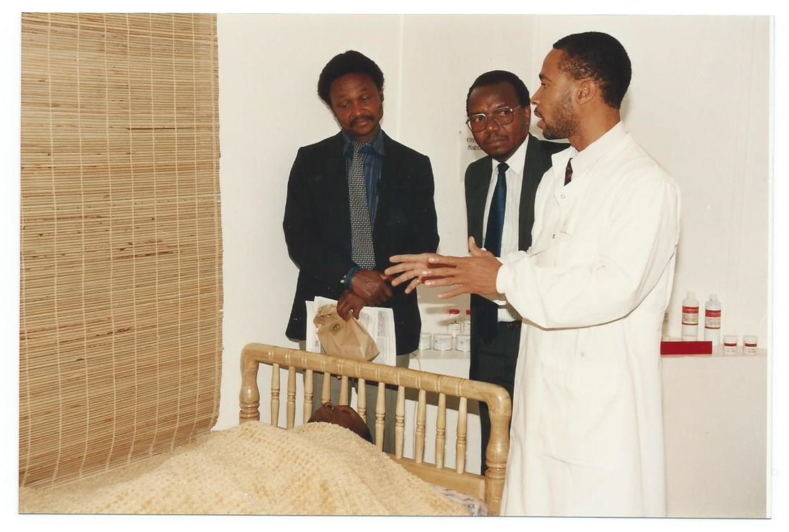 Dr. N. Nwoke, GIDE Researcher Demonstrates How GIDE's Affordable Technology of Papyrus Impregnated Papyrus Mat (left) is Used on the Wall in a Bed Room for Controlling Mosquitoes in East Africa. Note Person Protected is Lying Peacefully in Bed!