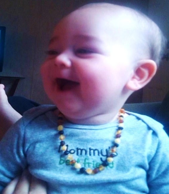 Happy teething baby while wearing a teething necklace from Staying Wild.