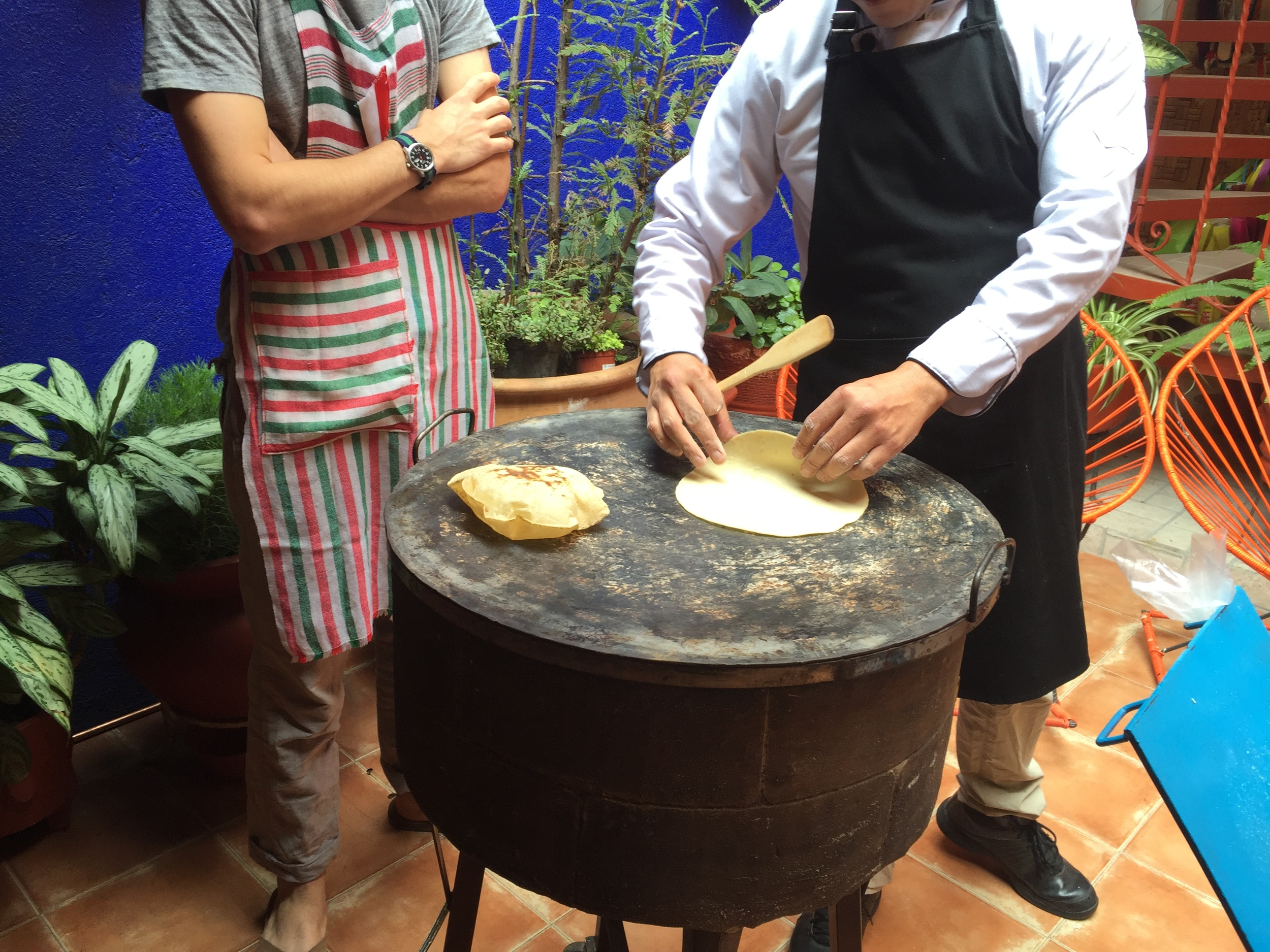 Chef Gerardo shows a fellow student from NYC how to gently slide the tortilla onto the tamal.