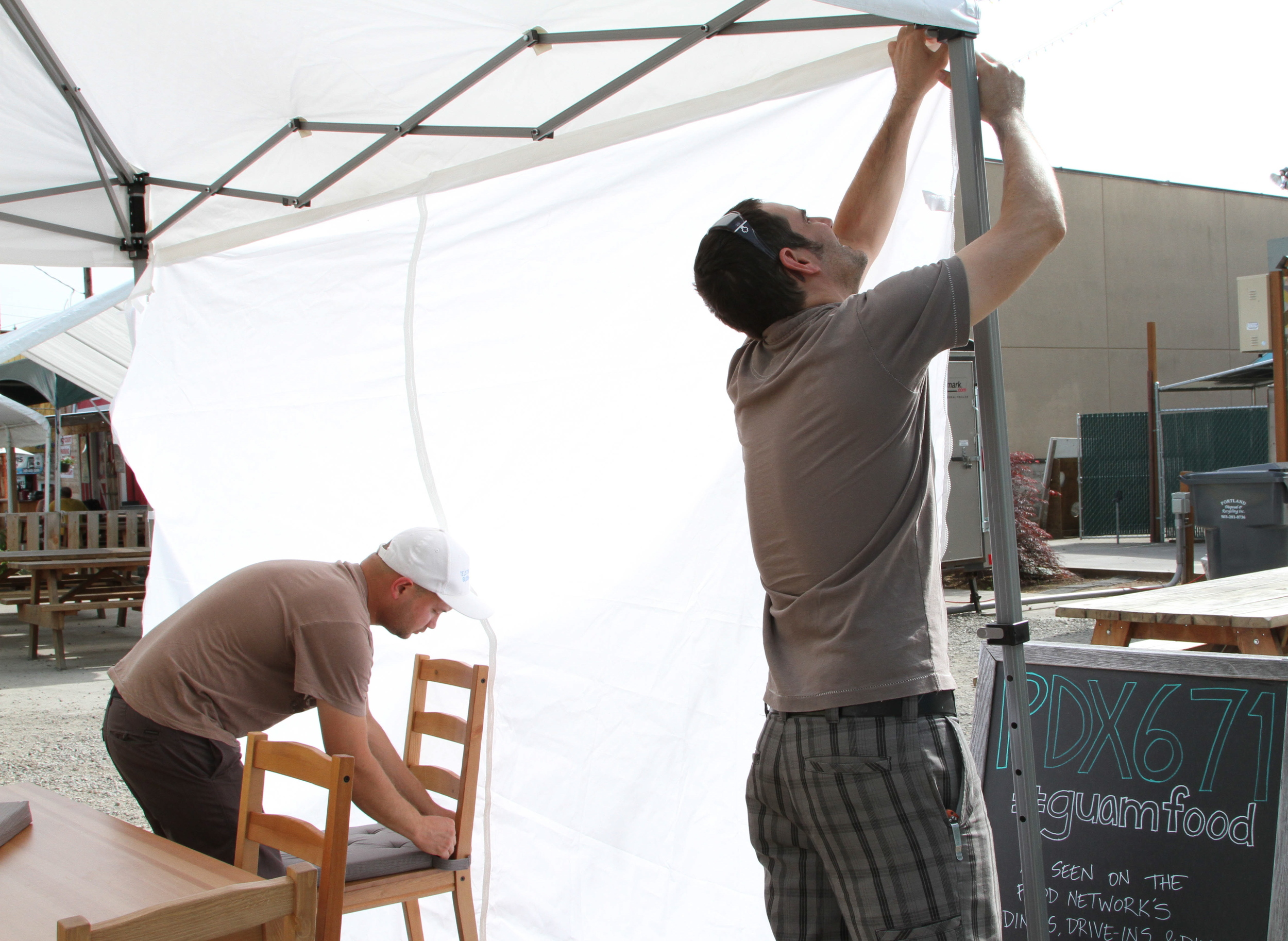 Keith setting up the chairs, while Carson puts the walls up onto the tent