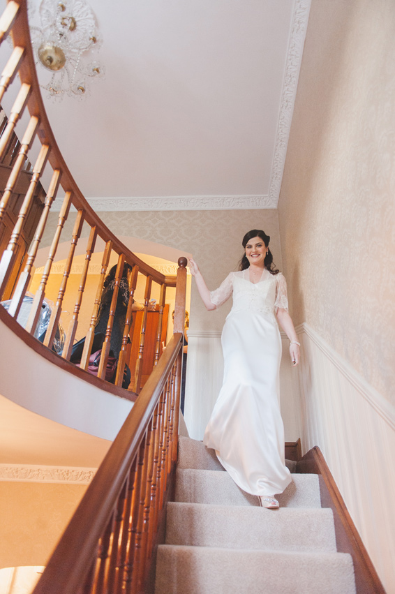 Bride walking down the stairs on the morning of the wedding