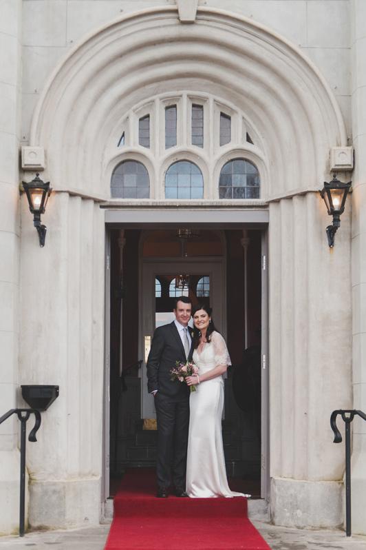 Bride and groom in doorway of bellingham Castle Hotel