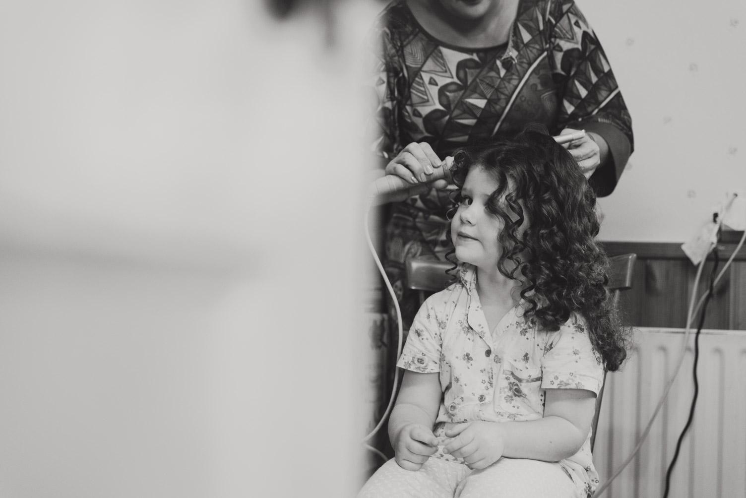 Flower girl on morning of wedding getting her hair done.