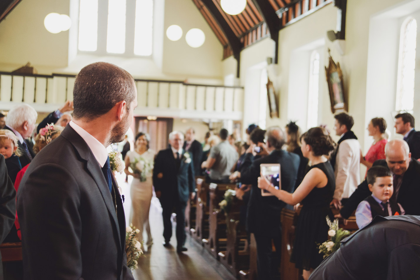 Groom looking at bride walking up the aisle in church. Wedding photography Meath.