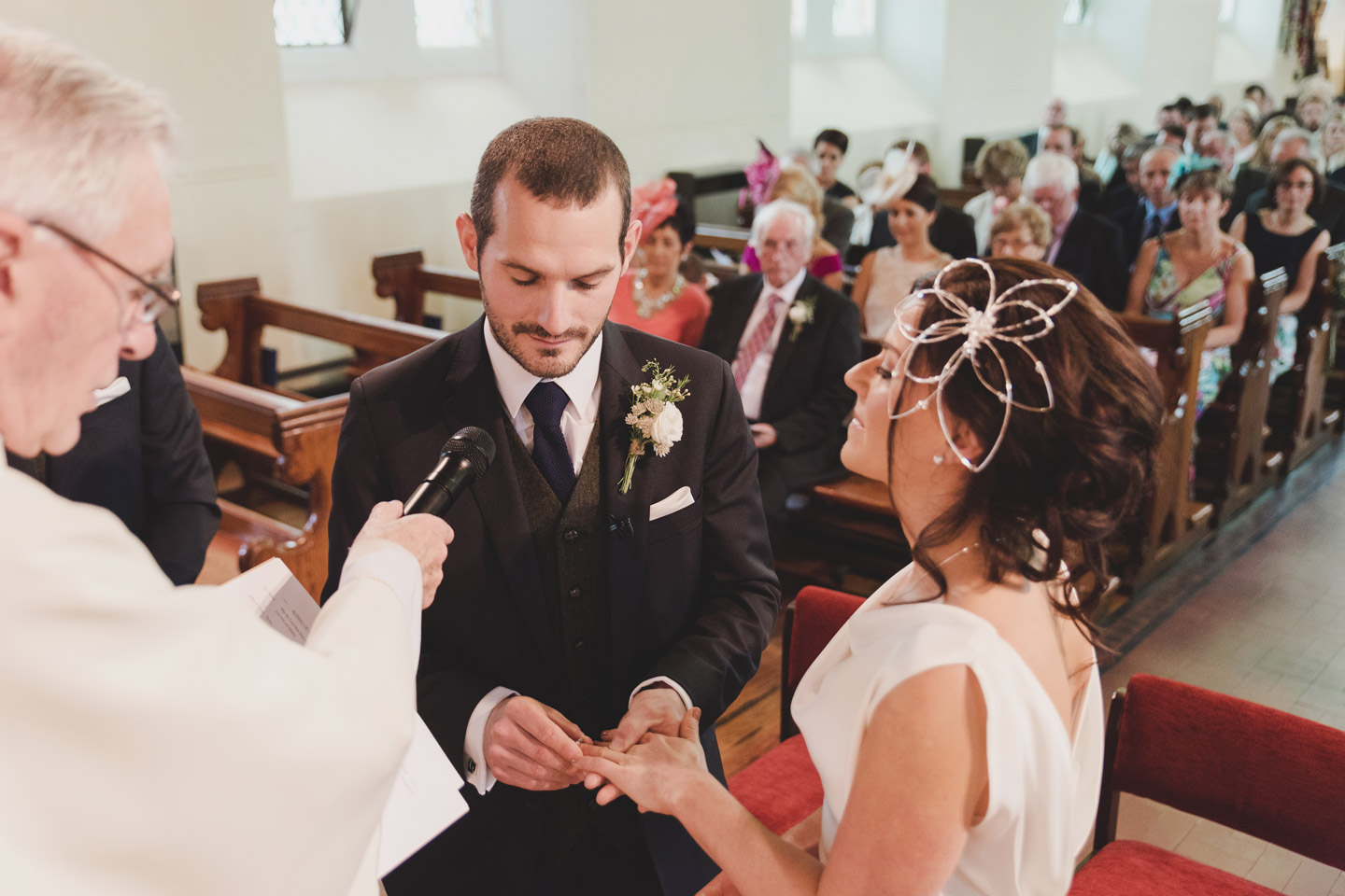 Groom putting ring on bride's finger in church. Weddings by KARA Wedding photography meath