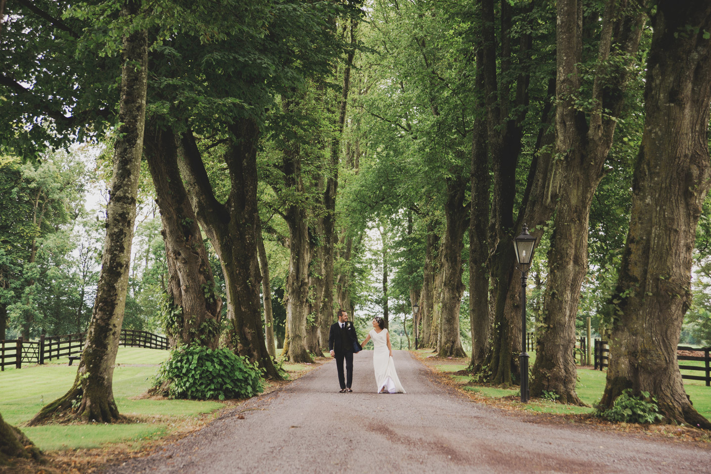 Bride and groom walking down a tree-lined avenue in Tankardstown House Meath Wedding photographers meath ireland