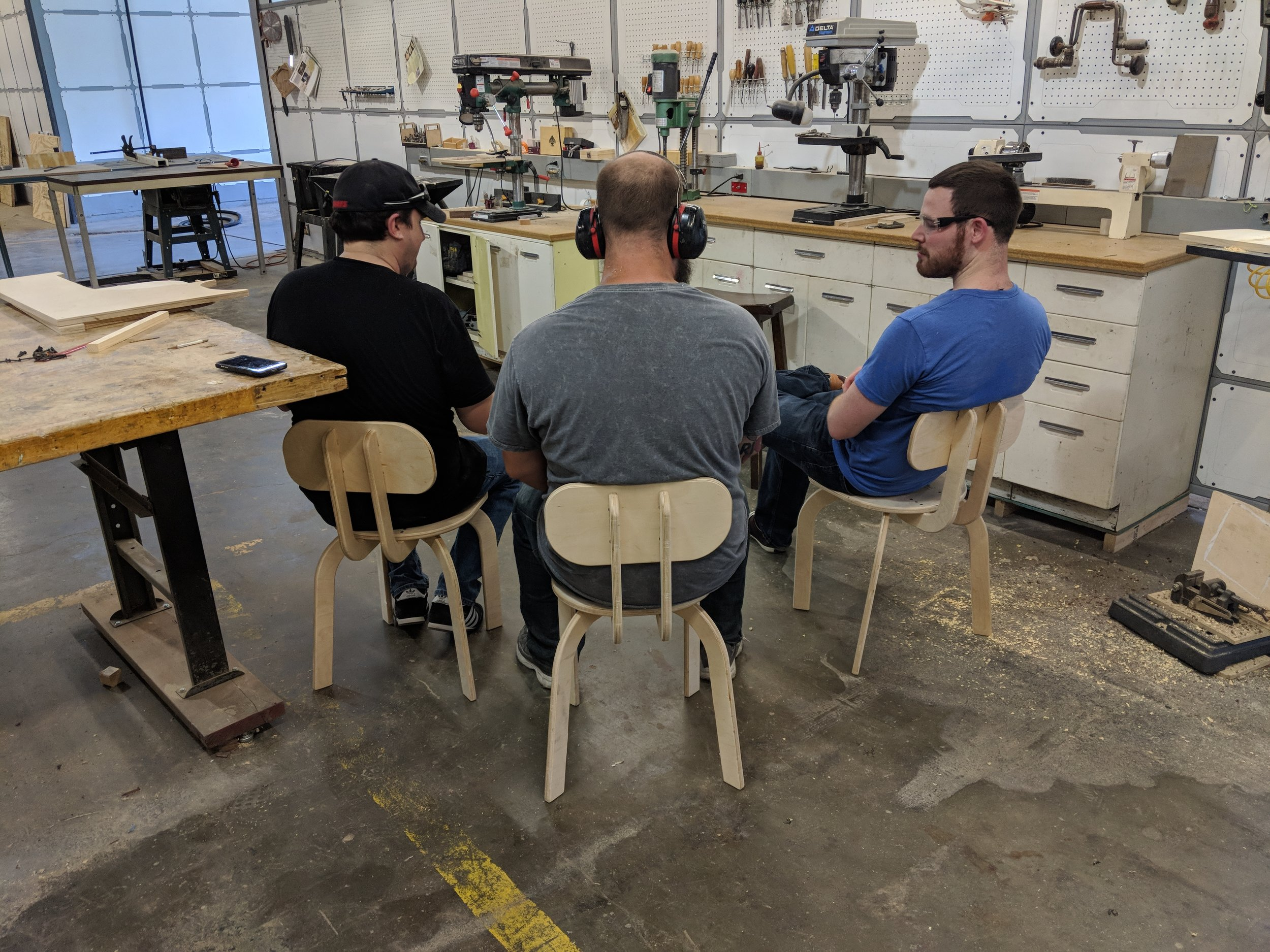 Three big men sitting on small Paramentric Chairs designed in Fusion 360