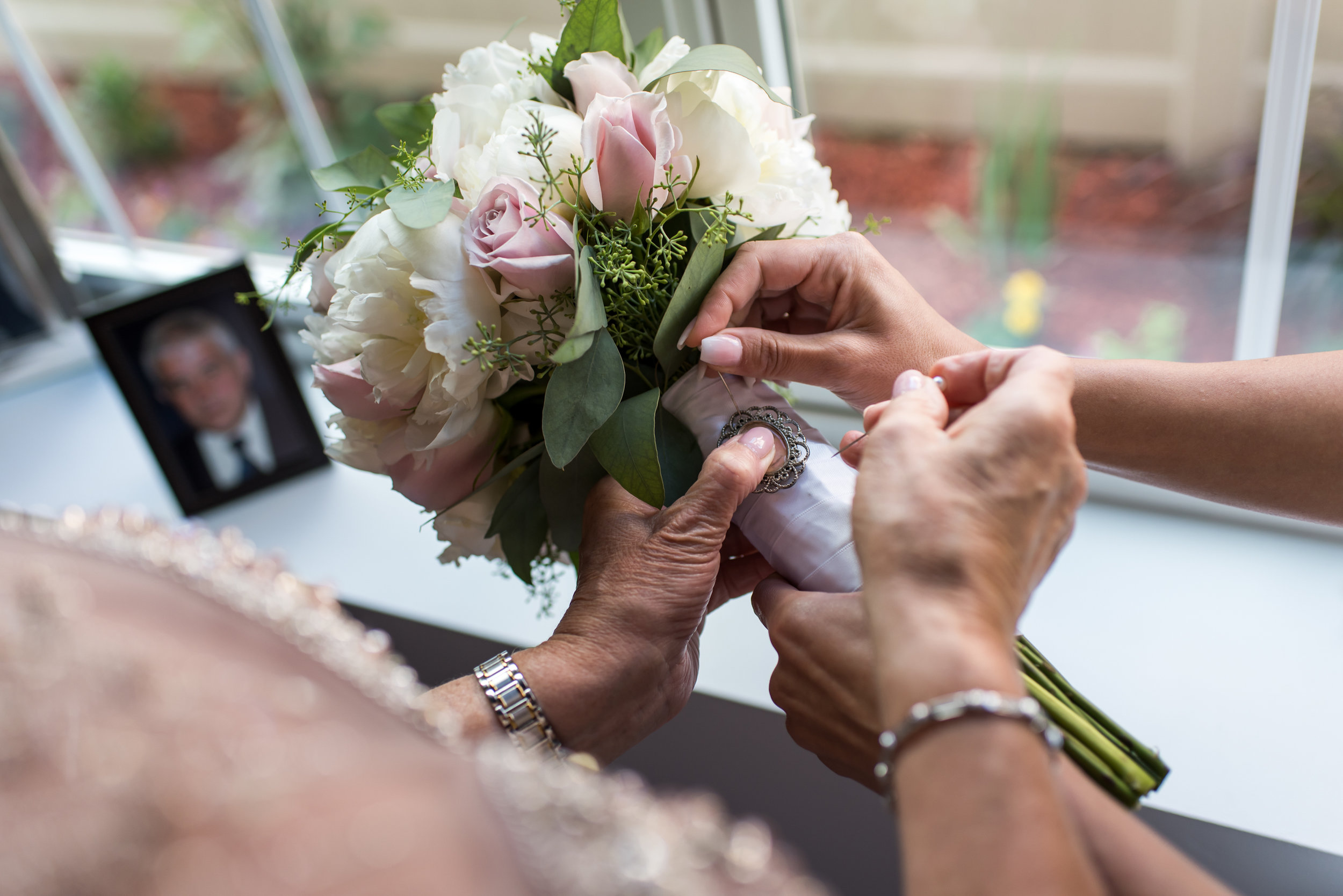 Stefy Hilmer Photography- bride and mom are pinning the deceased dad's photo onto the bouquet.jpg