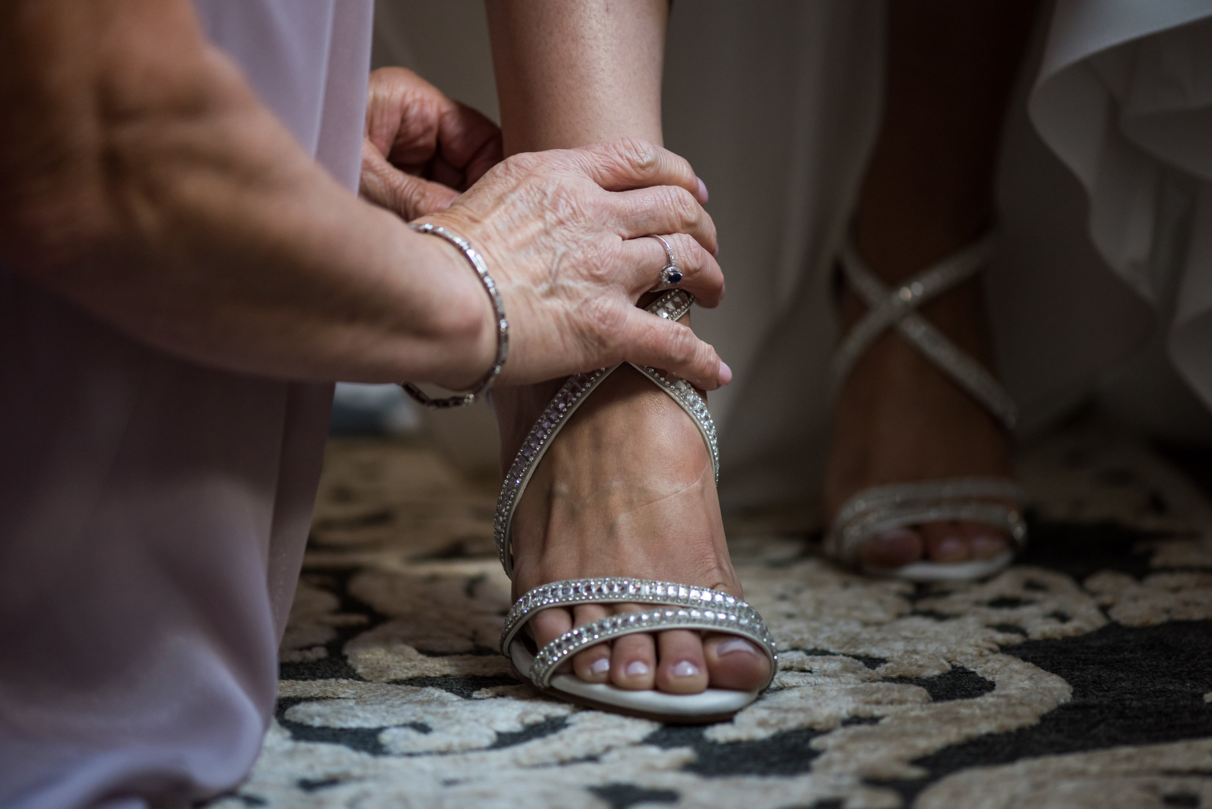 Stefy Hilmer Photography-mom is helping bride to put on wedding shoes.jpg