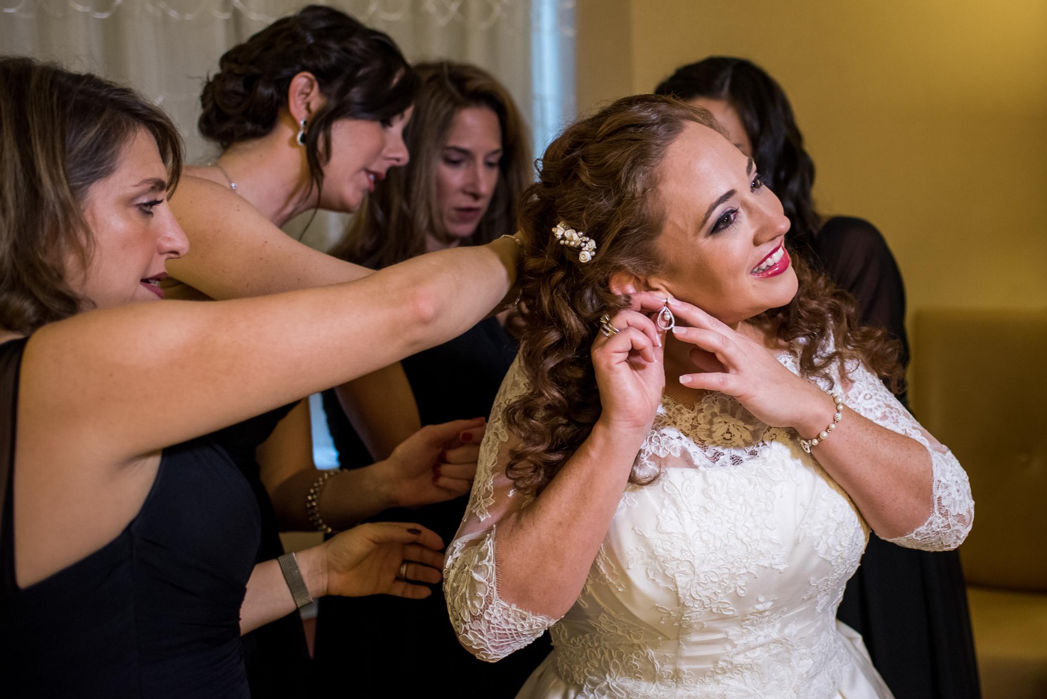 Stefy Hilmer Photography-bride is putting weddign jewlery on.jpg