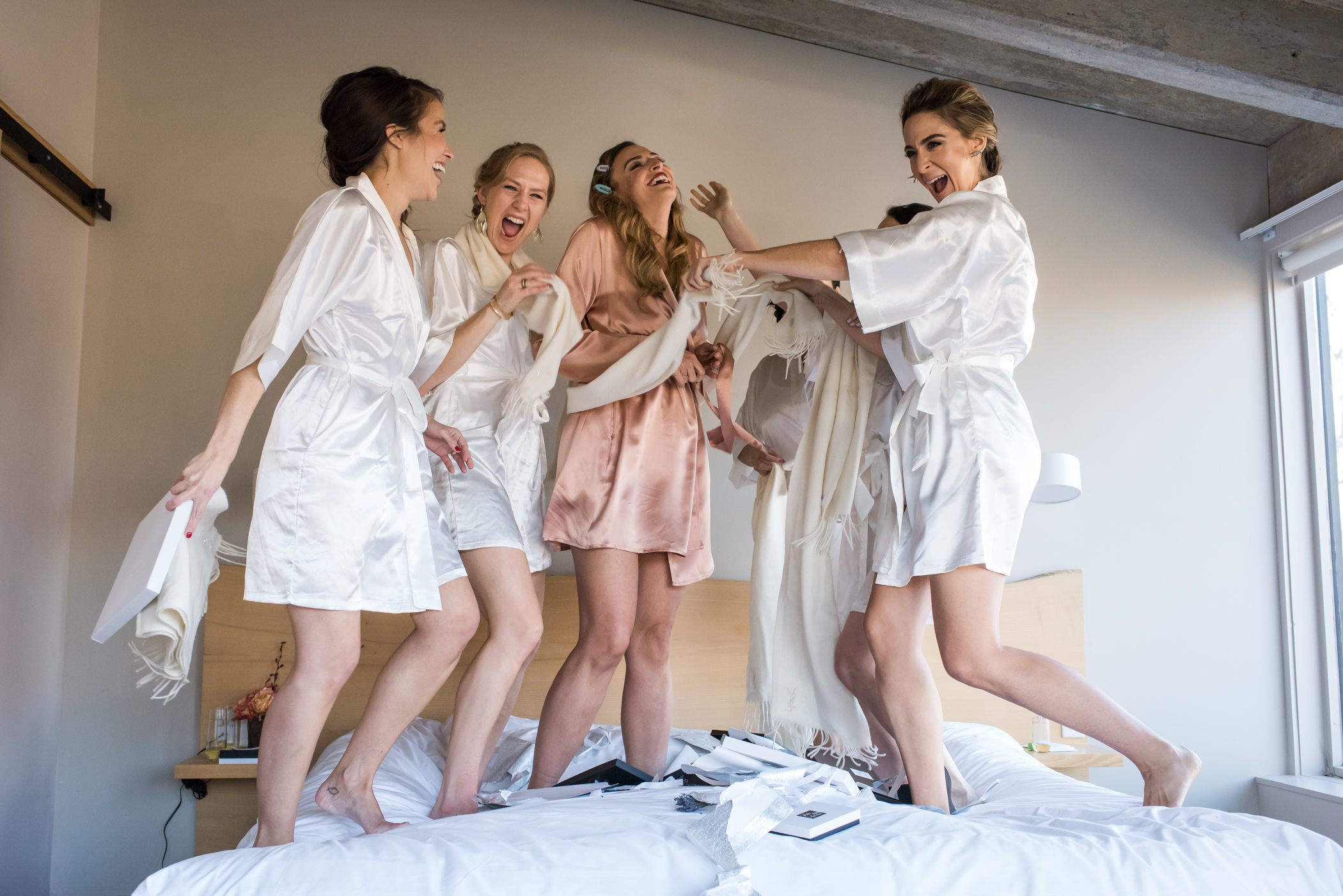 Stefy Hilmer Photography-bride is jumping on bed with bridesmaids.jpg