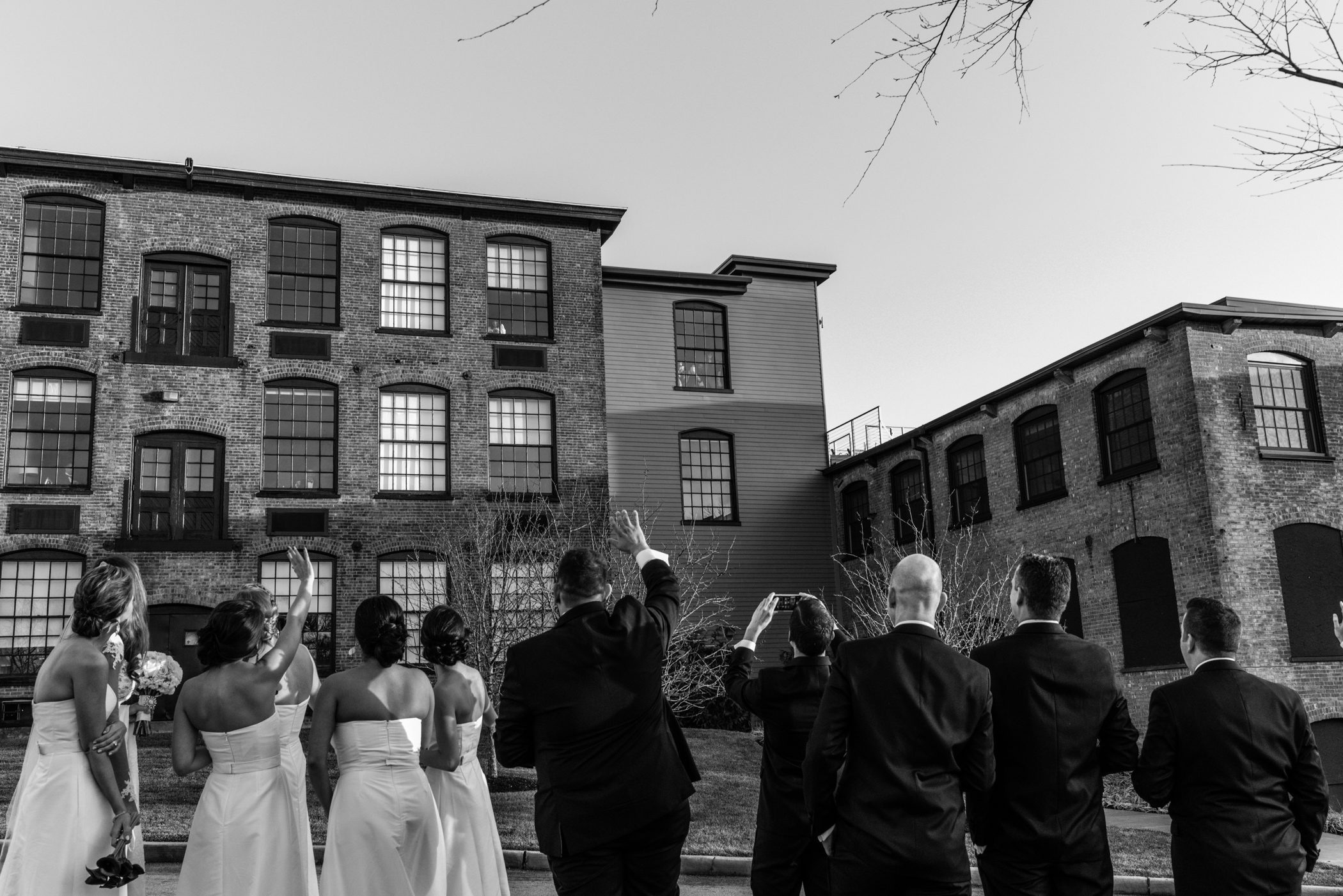 Stefy Hilmer Photography-candid photo people looking out the window down on bridal party during photo shoot.jpg