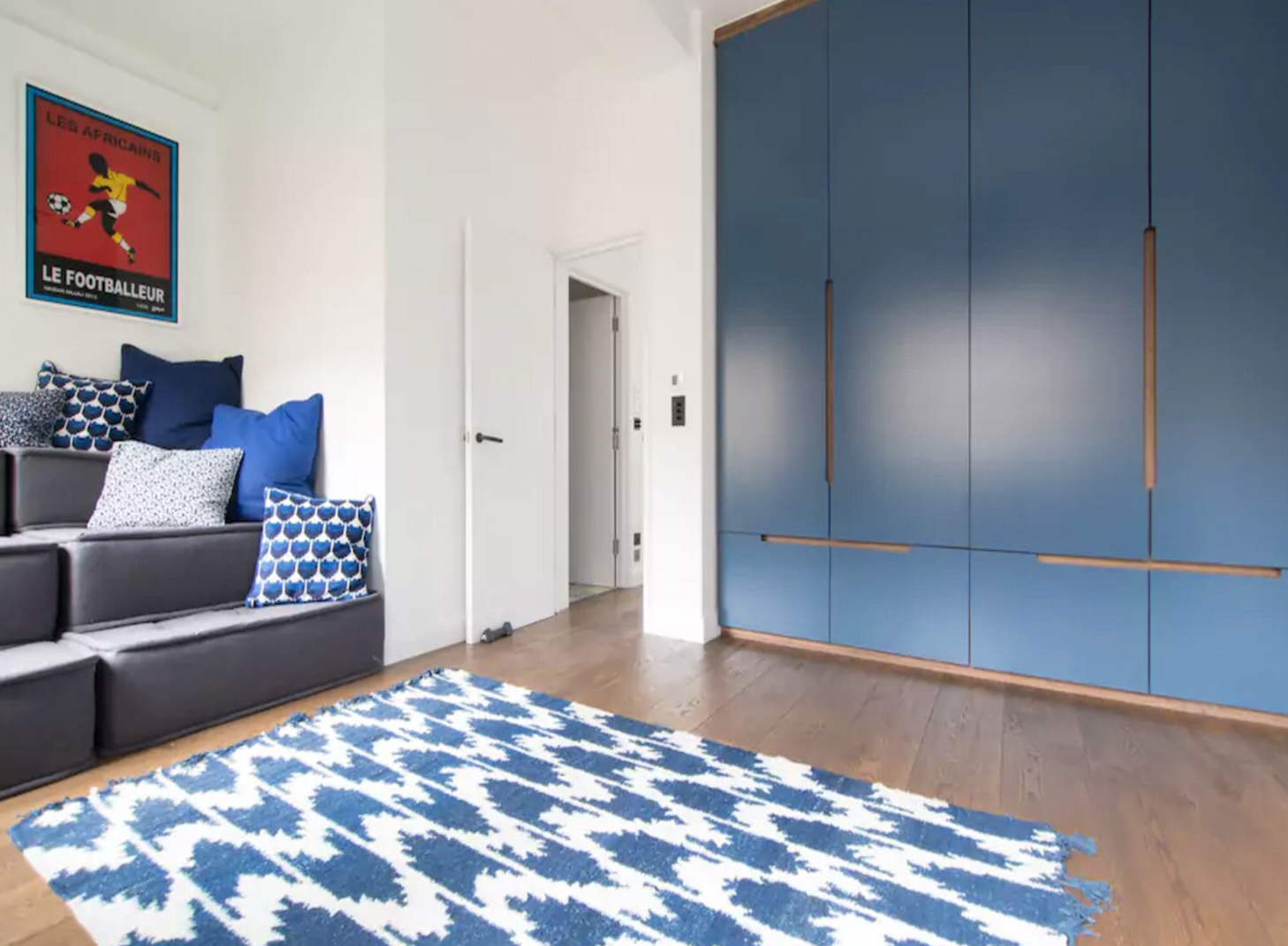 Doors in Farrow and Ball Stifkey Blue. Cabinetry in Walnut veneered MDF.