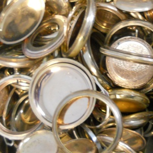 Photo of gold-filled pocket watch cases scrap that Specialty Metals customers have shipped to us for recycling and refining.