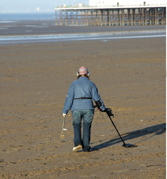 Now that the summer crowds are gone, it's the perfect time to search for precious metals on the empty beaches with a metal detector. Credit: TACrafts/iStock
