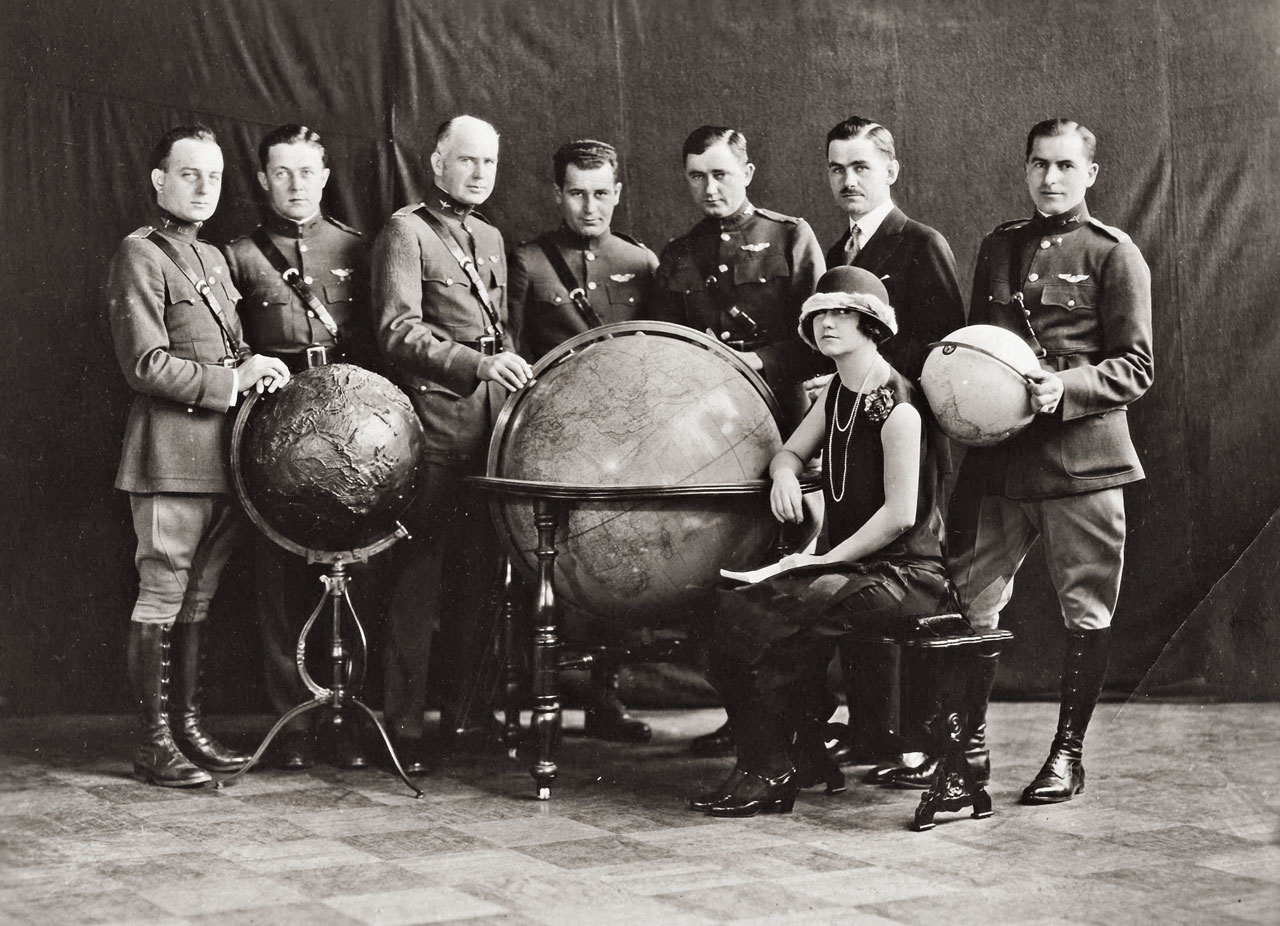 The six world fliers with adventurer and writer Lowell Thomas. From left to right: Arnold, Harding, Nelson, Wade, Smith, Lowell Thomas, Ogden and Mrs. Corliss Mosely, secretary to the pilots. (National Archives)