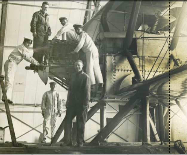 Japanese mechanics inspect the engine of one of the World Cruisers during one of the round-the-world aerial expedition's six stops in Japan.                        Photo credit: Smithsonian National Air and Space Museum / Milestones of Fligh t