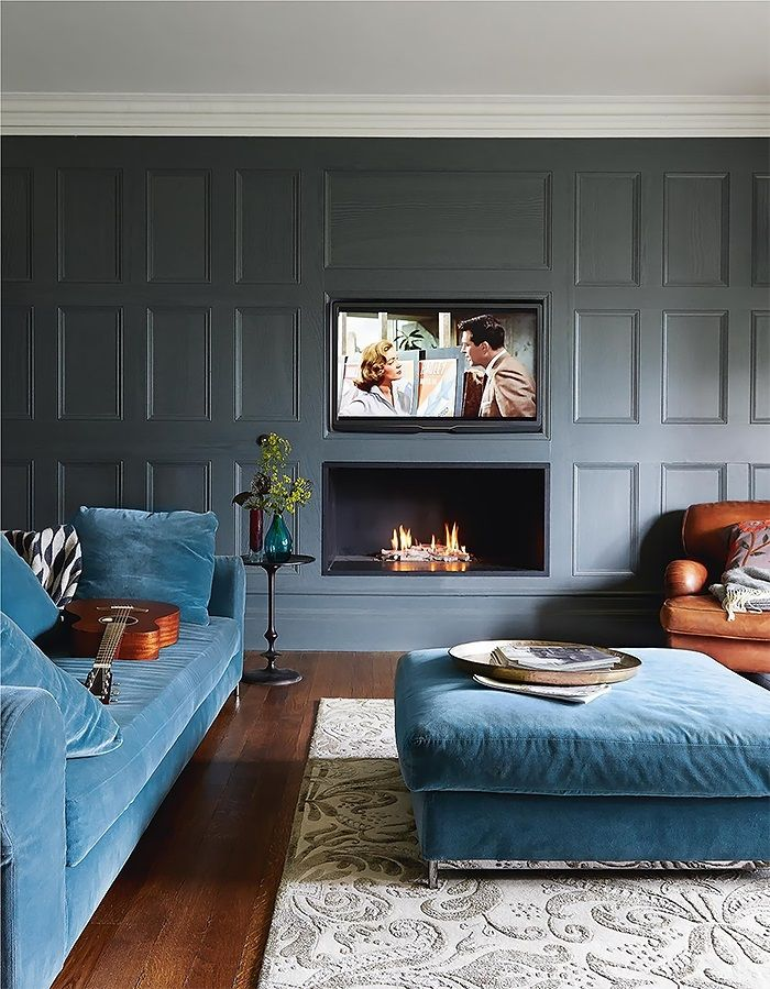 -via imgur.com / I think this whole situation rocks. Love the gray paneling,  the blue couch and ottoman, the club chair and the modern fireplace with it's matching flat-screen perched above.  (Don't love the rug, but that's okay...I'll take it!)